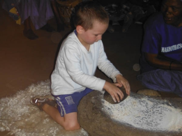 Learning how to grind millet with a grind stone, Lesotho